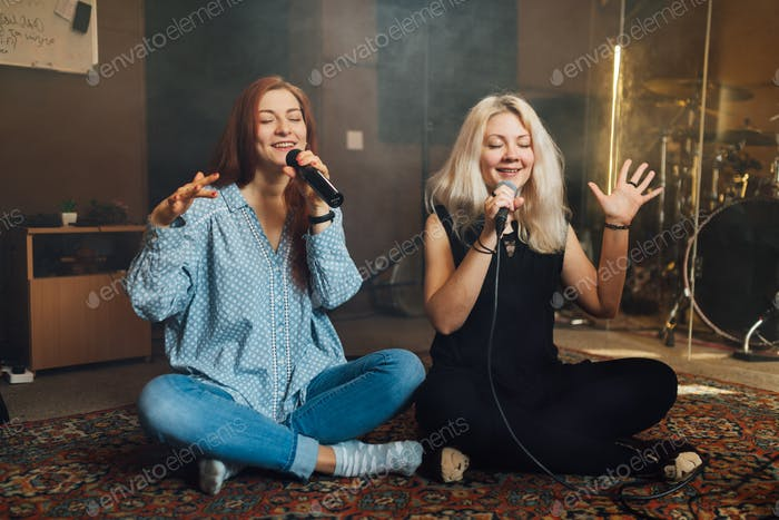 Two young woman sitting singing a duet