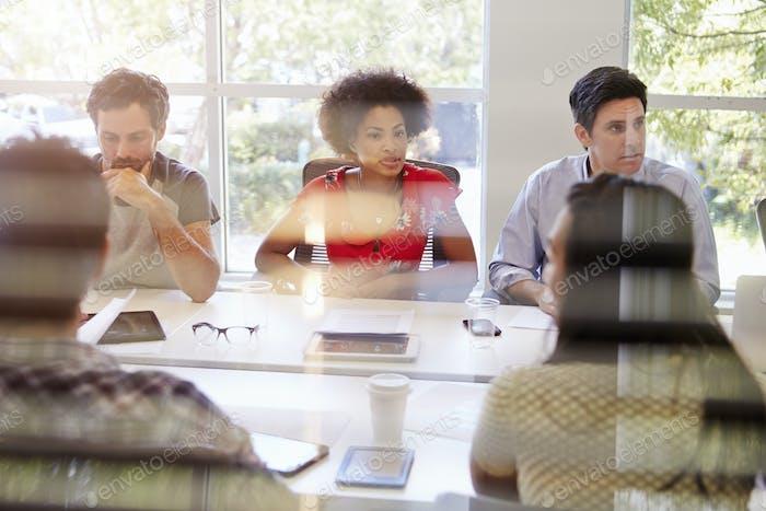 Designers Having Meeting Viewed Through Window