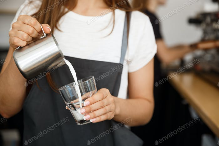 Coffee Business Concept - close-up lady barista in apron preparing and pouring milk in glass cup