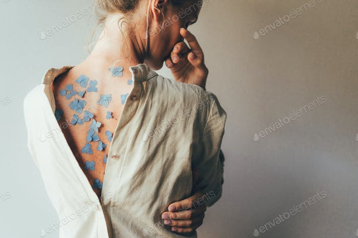 Rear view of a woman with a bare wall, blue hydrangea flower petals on her tanned skin.
