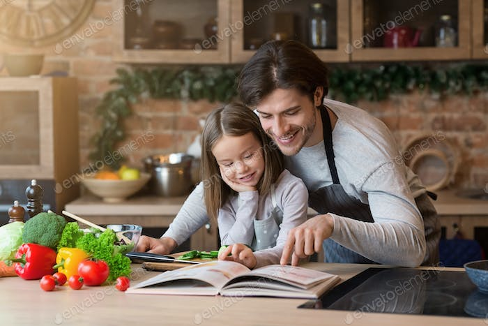 Happy dad and little daughter checking recipe in cookbook together