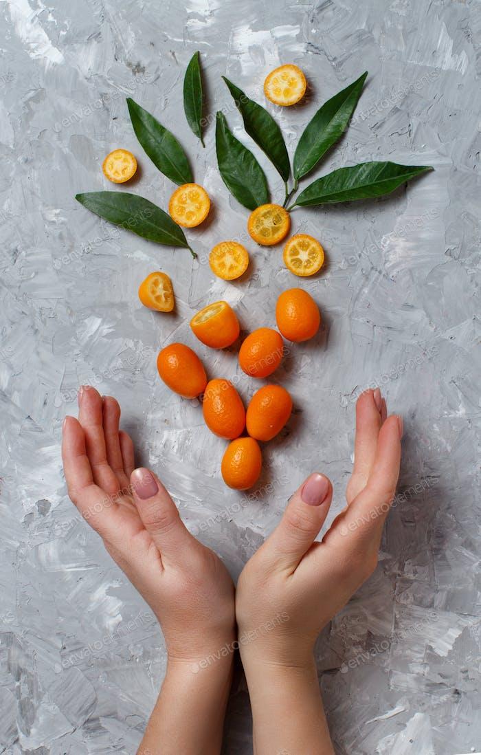 Kumquat fruits on a grey background