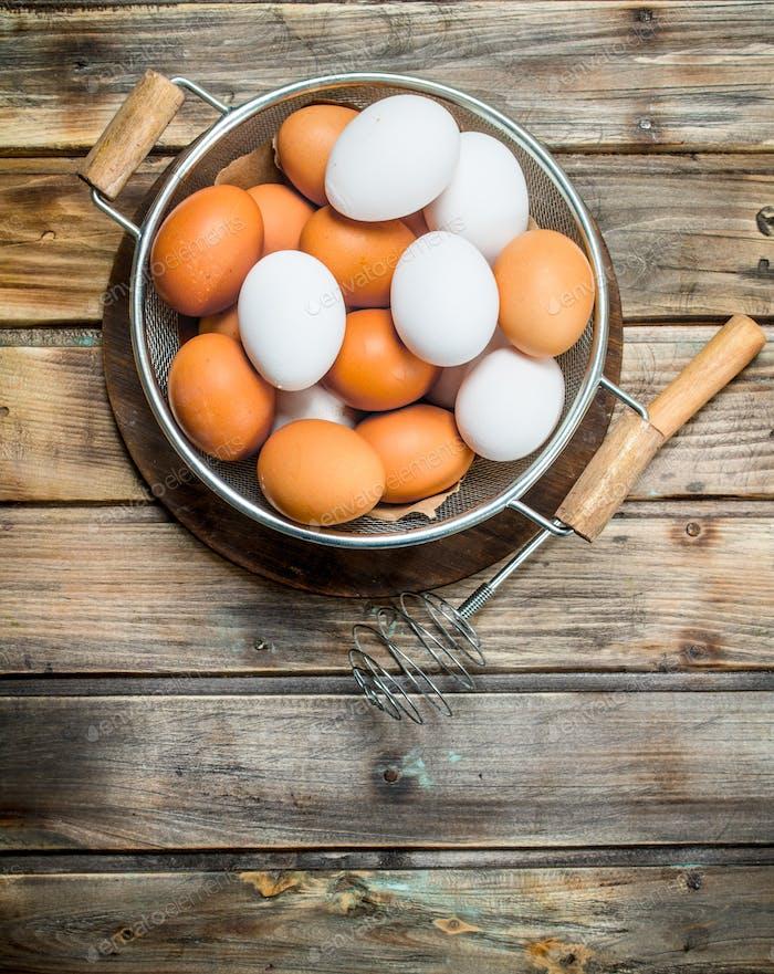 Eier in einem Topf mit einem Schneebesen.