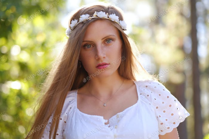 Freckled woman with circlet of flower on her head.