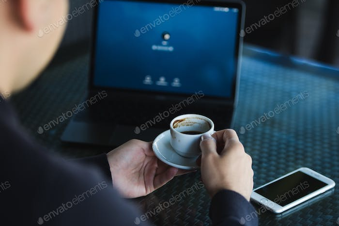 Fresh coffee for great ideas. Top view man working on laptop and holding cup of coffe while sitting