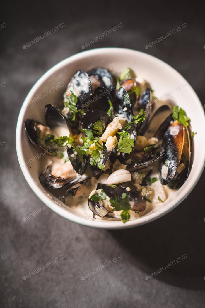 Mussels in sashes in sauce in a bowl on black slate