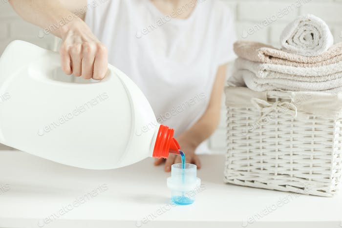 Woman pouring detergent into cap on table, close-up. Laundry concept