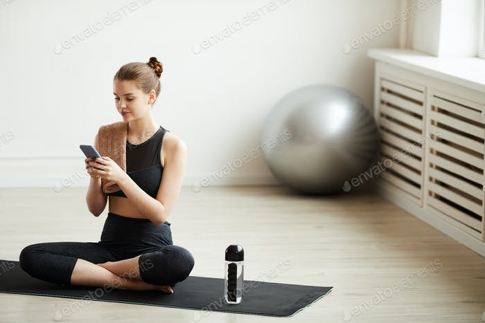 Fit woman using her phone