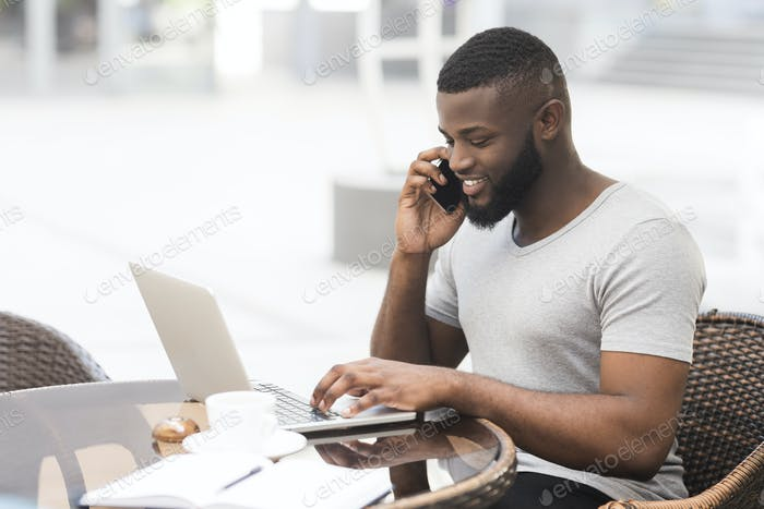 Young african guy working on laptop and talking by phone