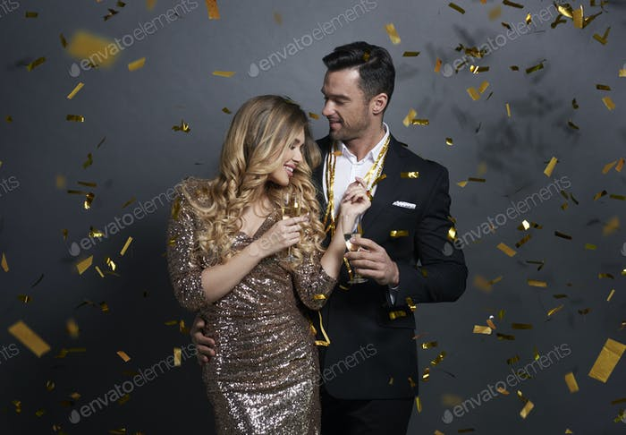 Couple embracing and drinking alcohol at studio shot