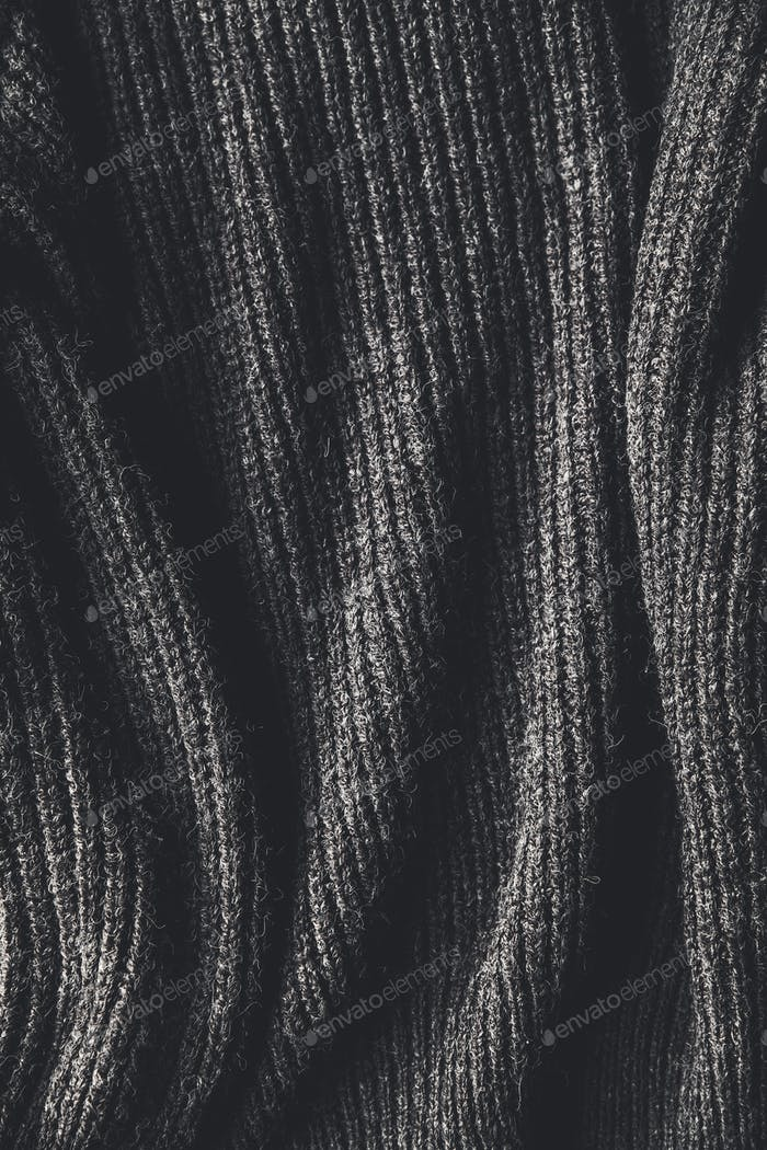 Texture of a black knitted sweater closeup. dark knitted wool material background