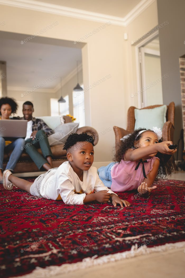 African American sibling lying on floor and watching television while parents using laptop