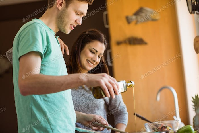Cute couple preparing food together at home in the kitchen