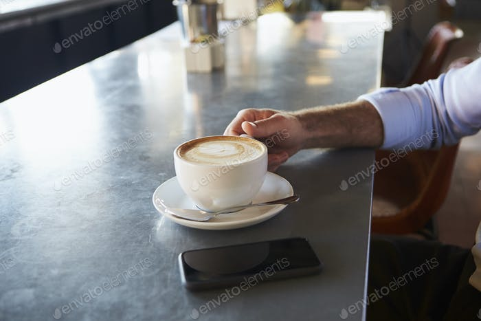 Close Up Of Man With Mobile Phone On Counter Of Coffee Shop