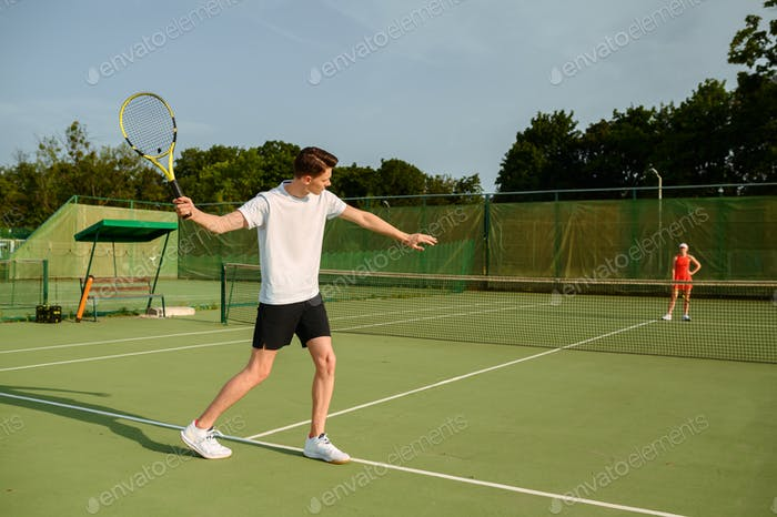 Male tennis player with racket hits the ball