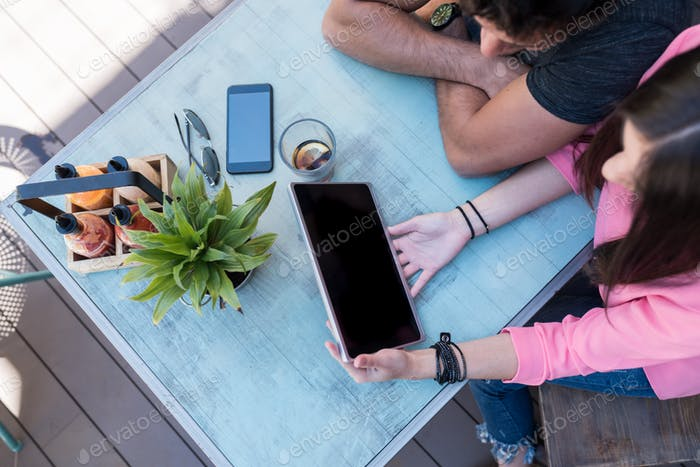 Top view of people with gadgets on a table outside