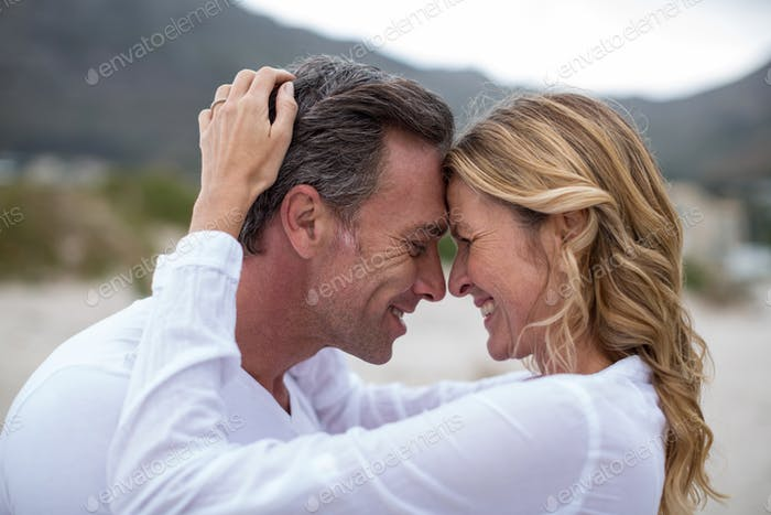 Mature couple embracing each other on the beach