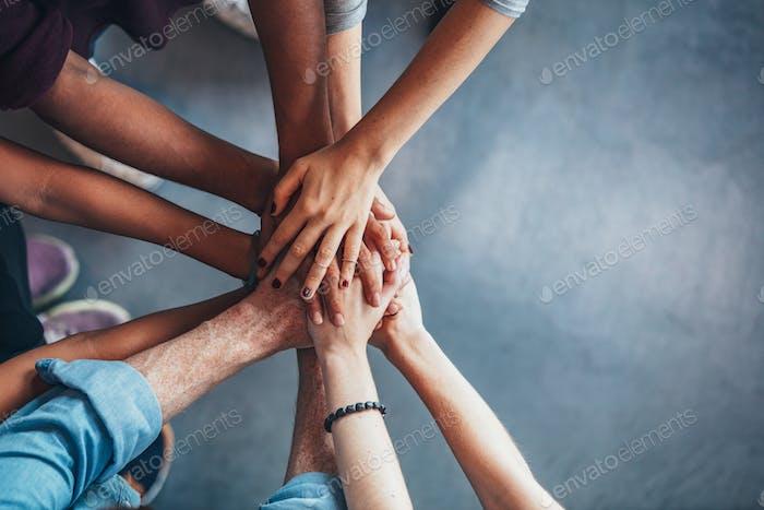 Stapel von Händen, die Einheit und Teamarbeit zeigen