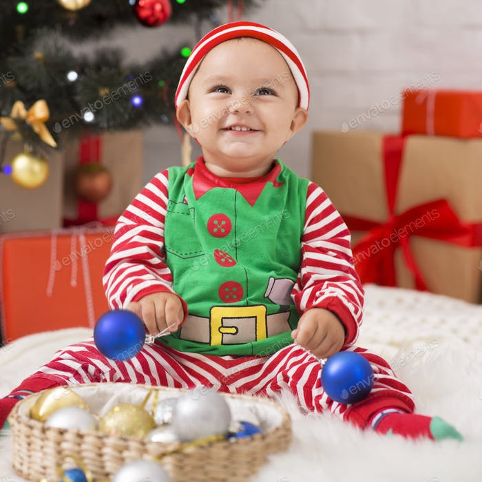 Happy baby elf with Christmas decorations laughing