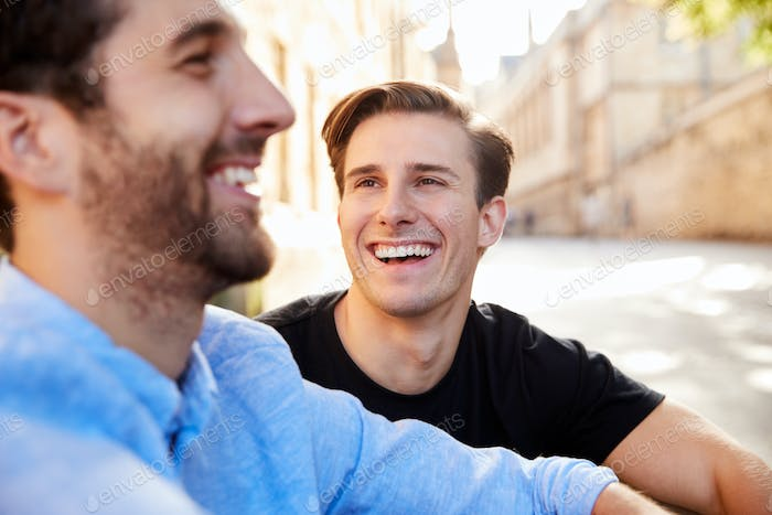 Loving Male Gay Couple On Vacation Walking Along City Street