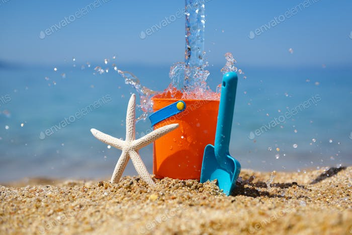 Bright plastic сhildren's beach toys and a starfish on sand near sea. Summer vacation concept
