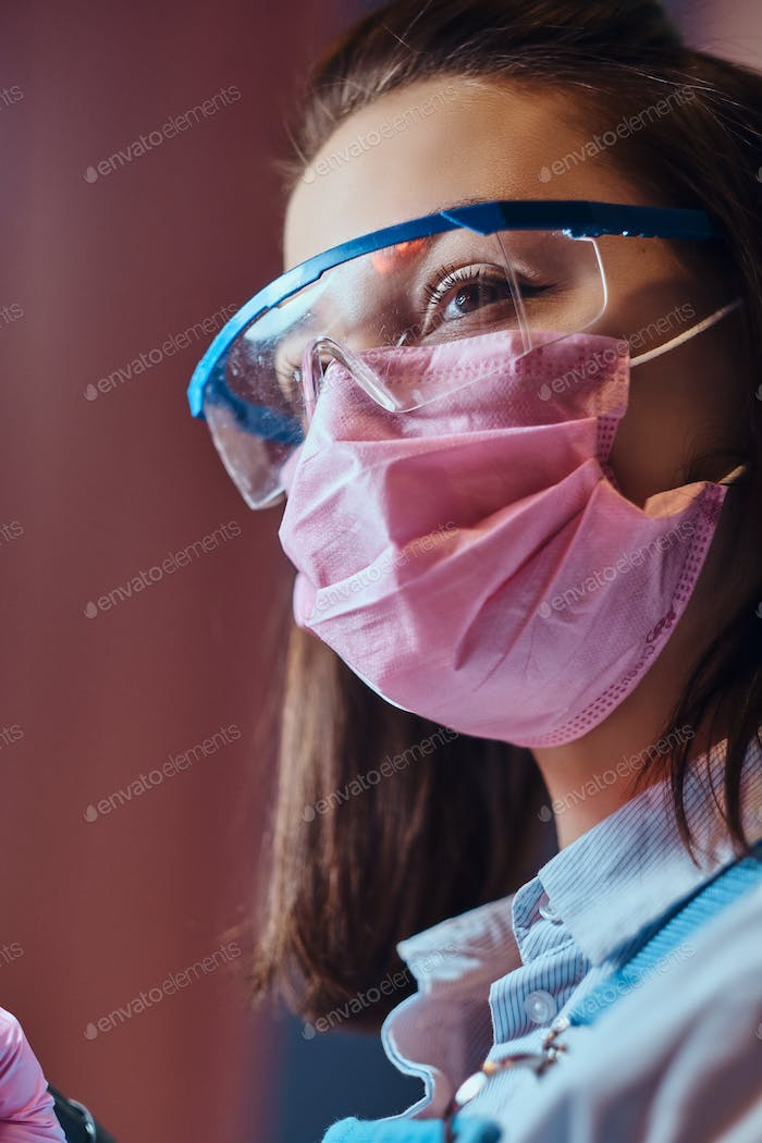 Portrait of young pensive manicurist in protective glasses and mask.