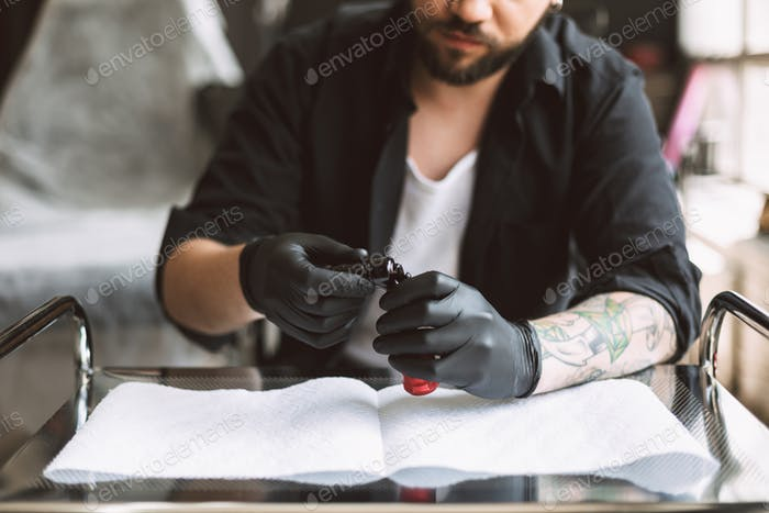 Close up professional tattooer in black gloves preparing equipme