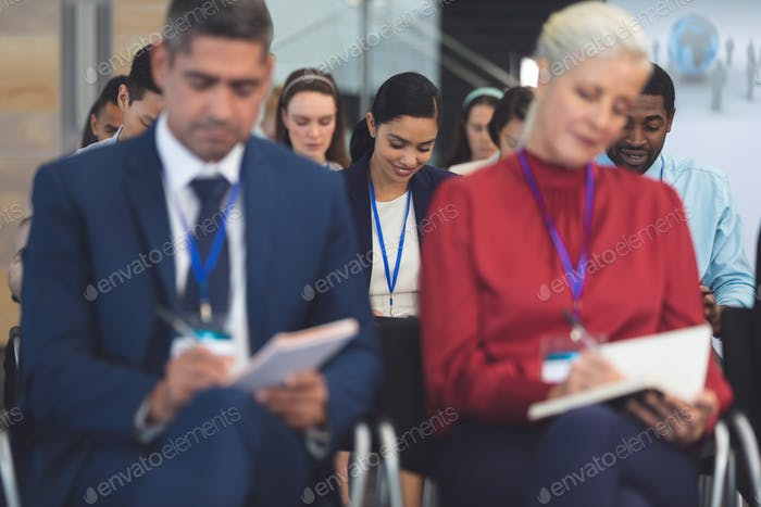 Businesswoman writing on notepad in business seminar in office building