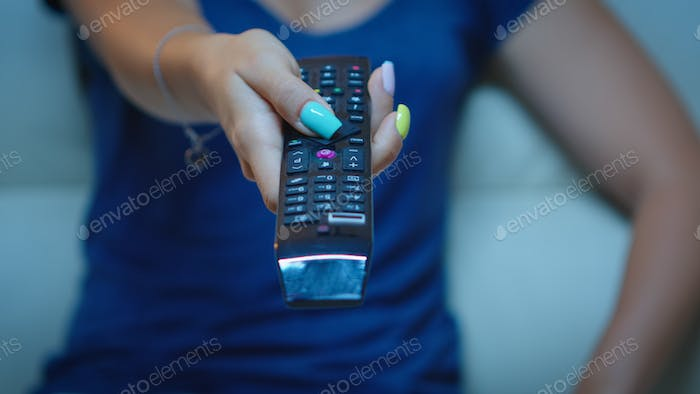 Close up of hand changing TV channels