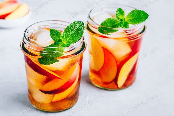 Homemade peach iced tea or lemonade with fresh mint and ice cubes in glass jar