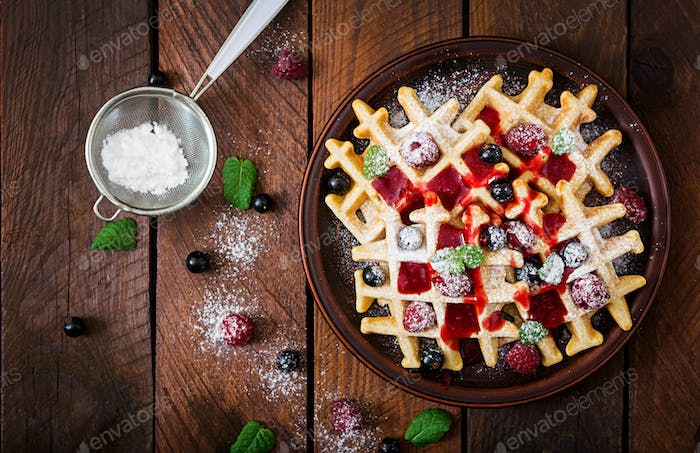 Belgium waffles with raspberries and syrup on a plate. Flat lay. Top view