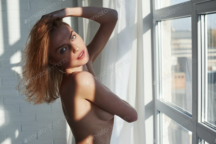 The woman meets the morning. Young red haired girl with bare chest stands near the window at daytime