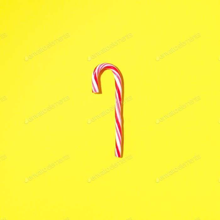 Christmas candy cane on yellow background with copy space. Top view. Greeting card on Christmas and