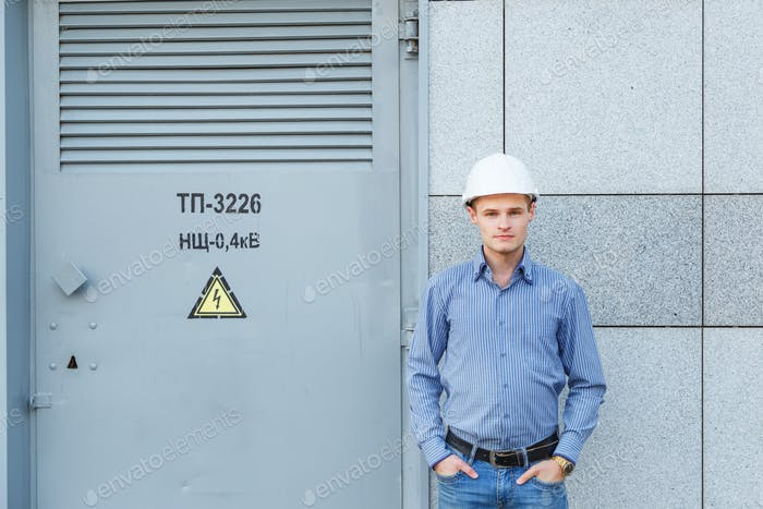 Portrait of young engineer at the transformer station