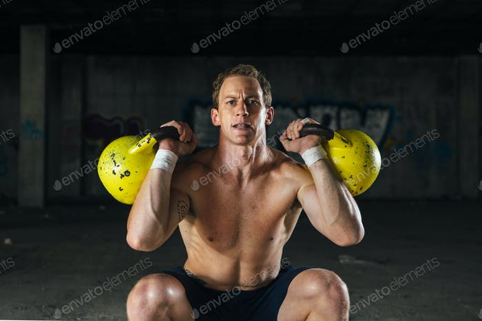 Male working out with dumbbells in hands
