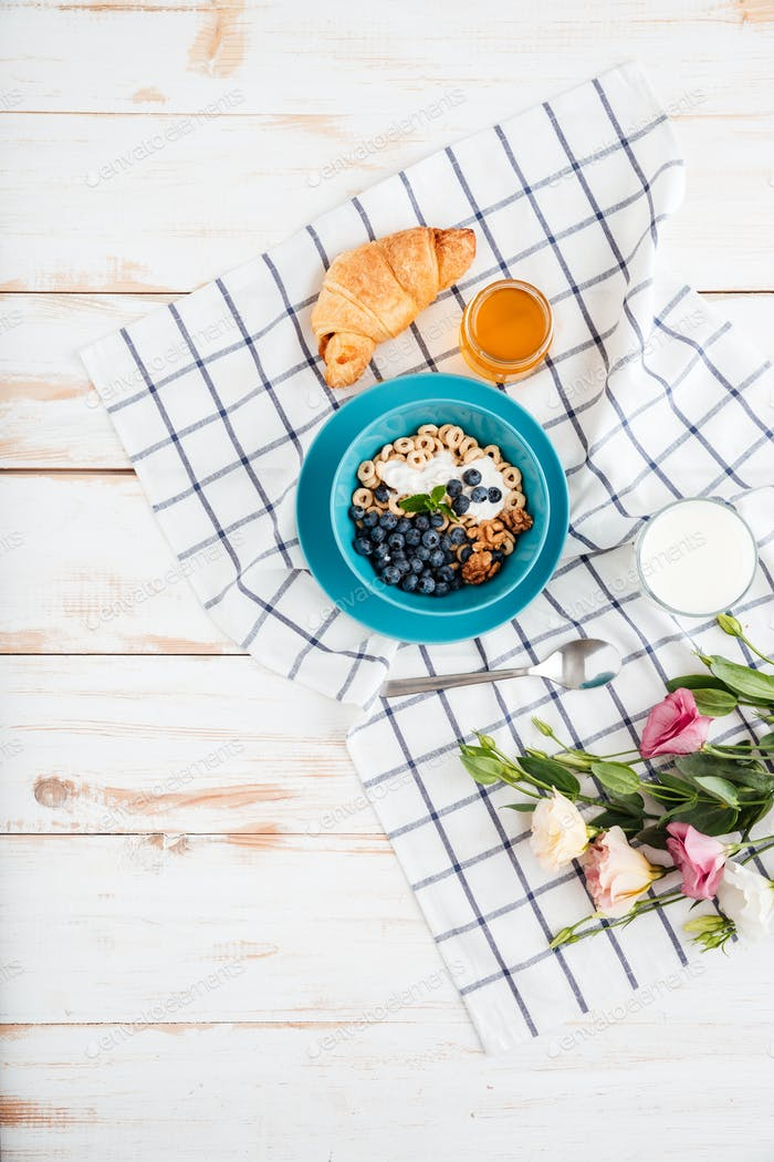 Oat cereals with berries and cream, cup of milk, flowers