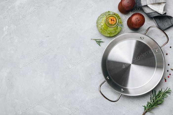 Leere Paella-Pfanne oder Auflauf aus Edelstahl mit Rosmarin und Gewürzen zum Kochen vorbereiten.