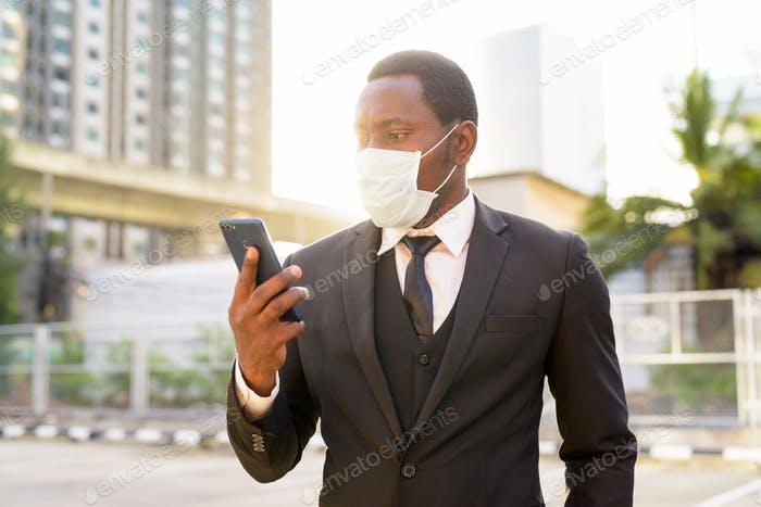 Portrait of African businessman with mask using phone in the city streets