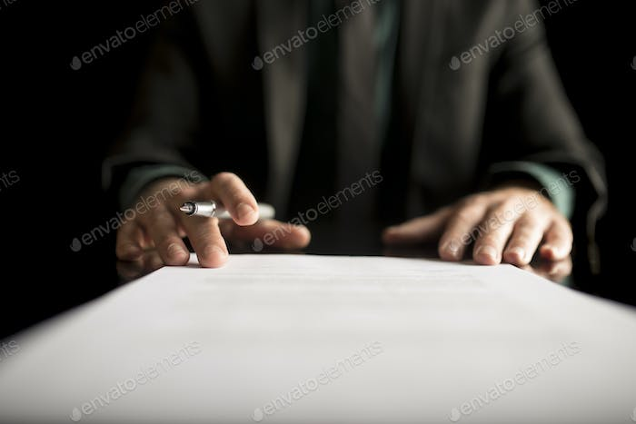 Businessman in business suit holding a fountain pen