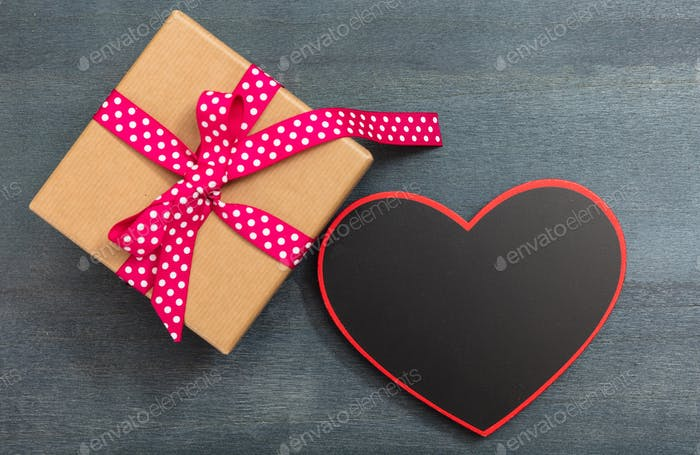 Valentine's day. A blank heart shape board and a gift box on blue background, copy space, top view