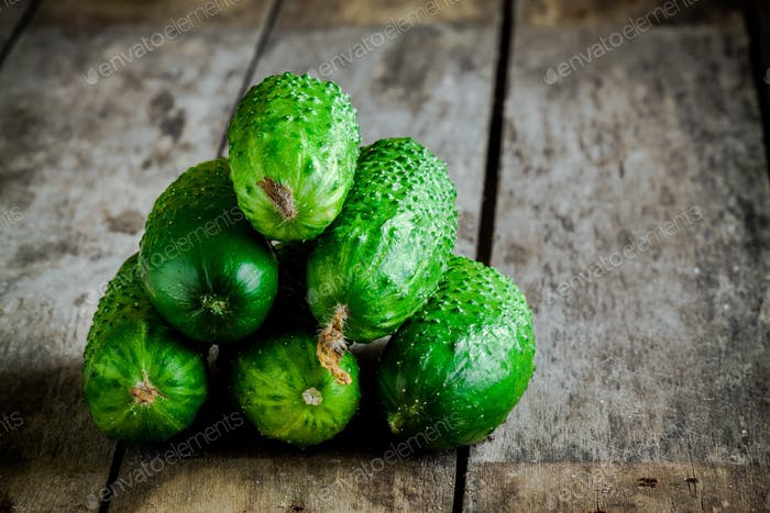 heap of fresh cucumbers on wooden table