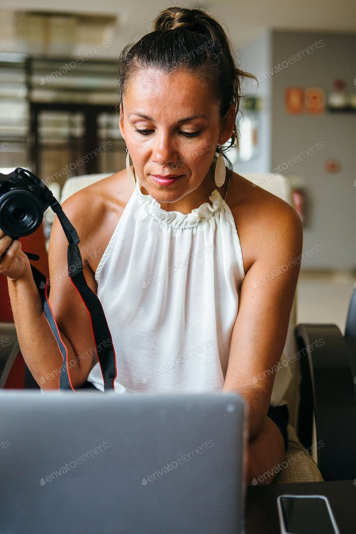Woman working with laptop and photo camera