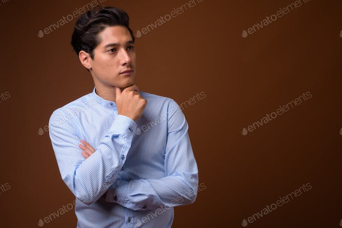 Young multi-ethnic handsome businessman against brown background