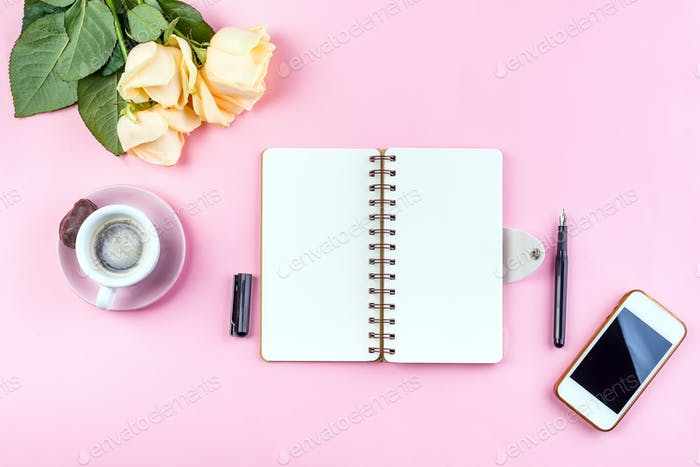 Morning coffee mug for breakfast, ephone, notebook, pencil and rose on pink table top view . Woman