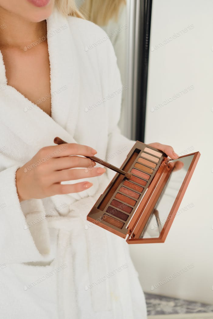 Woman in white bathrobe holding beautiful eye shadow palette with little mirror and brush in hands