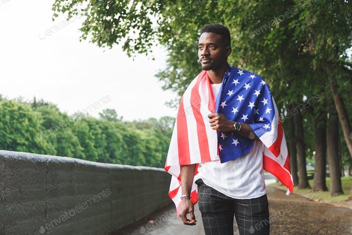 Afro amerikanischer Mann mit USA-Flagge auf seinen Schultern steht im Freien. Tag Sommer