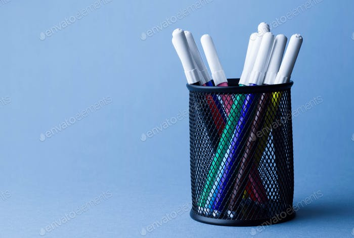 Colorful magic markers in a pencil box holder