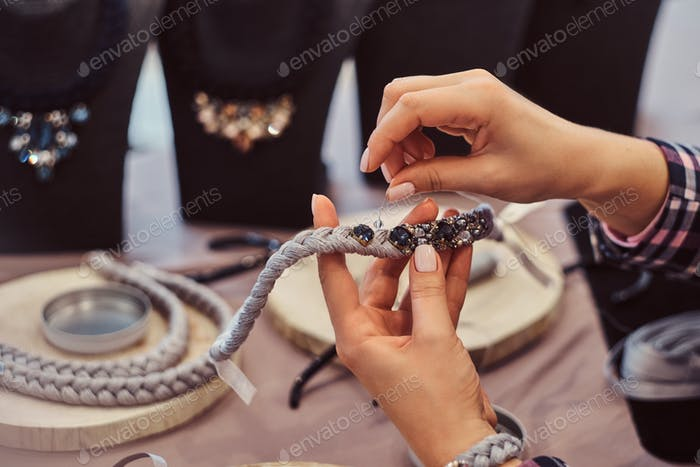 Close-up photo of a woman's hands who makes handmade necklaces