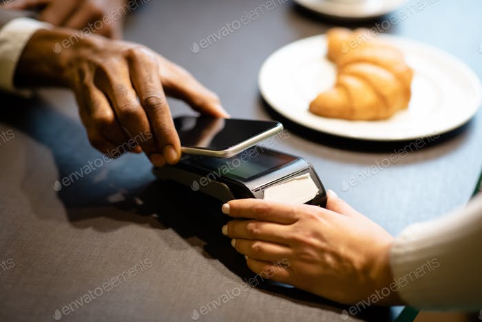 Afro businessman paying with his cellphone at the bar