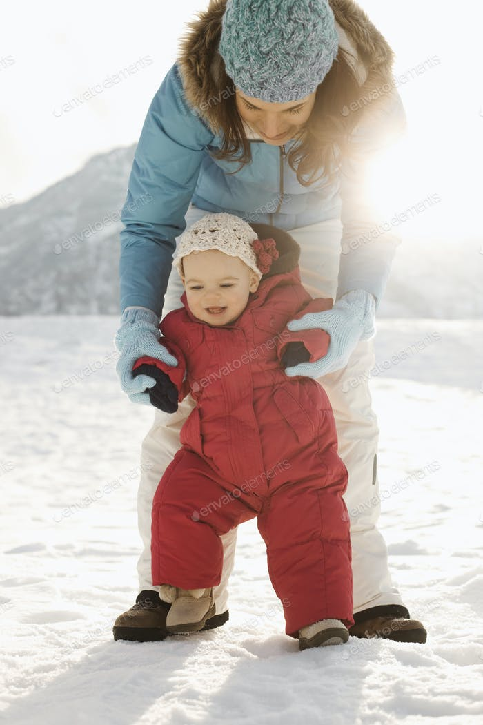 A mother and baby outdoors in the snow, a baby upright learning to walk.